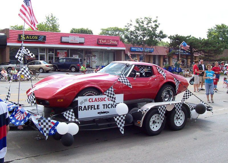 Red Car on a Trailer Being Shown Off in a Parade